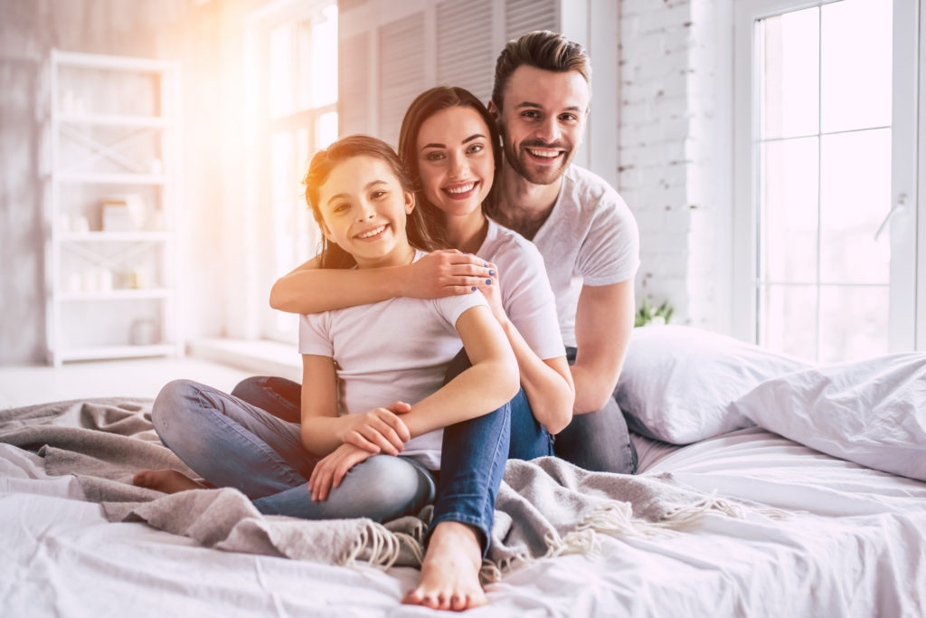 smiling family sitting on bed