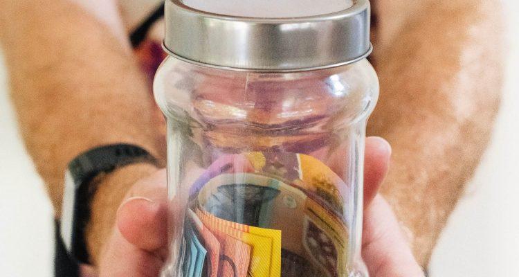 man holding a jar full of money