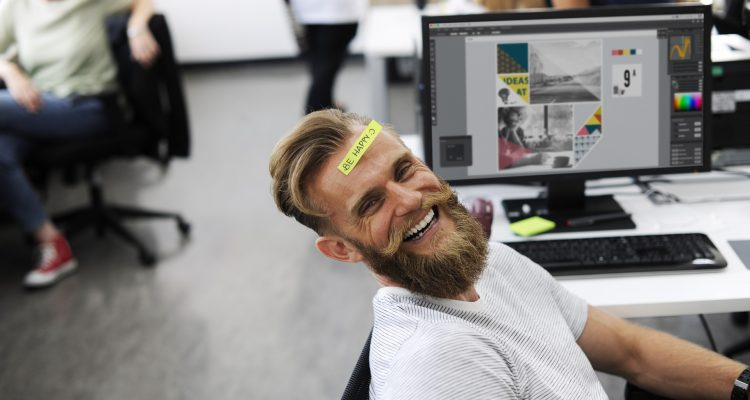 man smiling with sticky note on his head